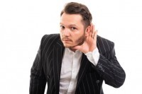 Portrait of business man showing can't hear gesture isolated on white background with copyspace advertising area